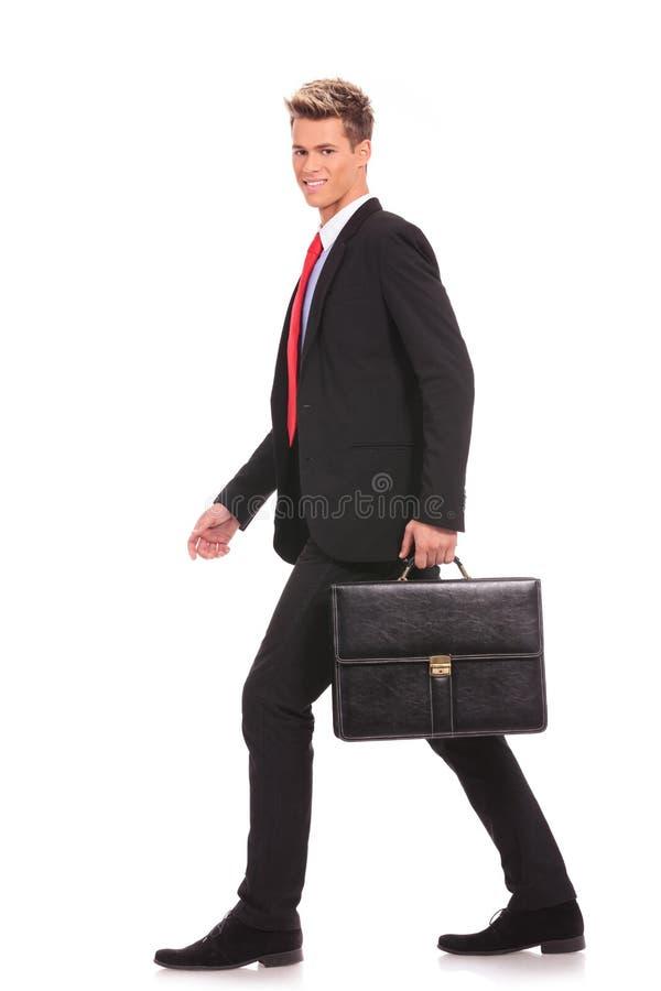 暂挂公事包和走的商人 库存照片