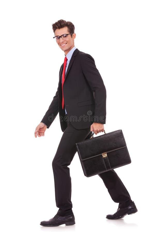 暂挂公文包和走的商人 免版税库存图片