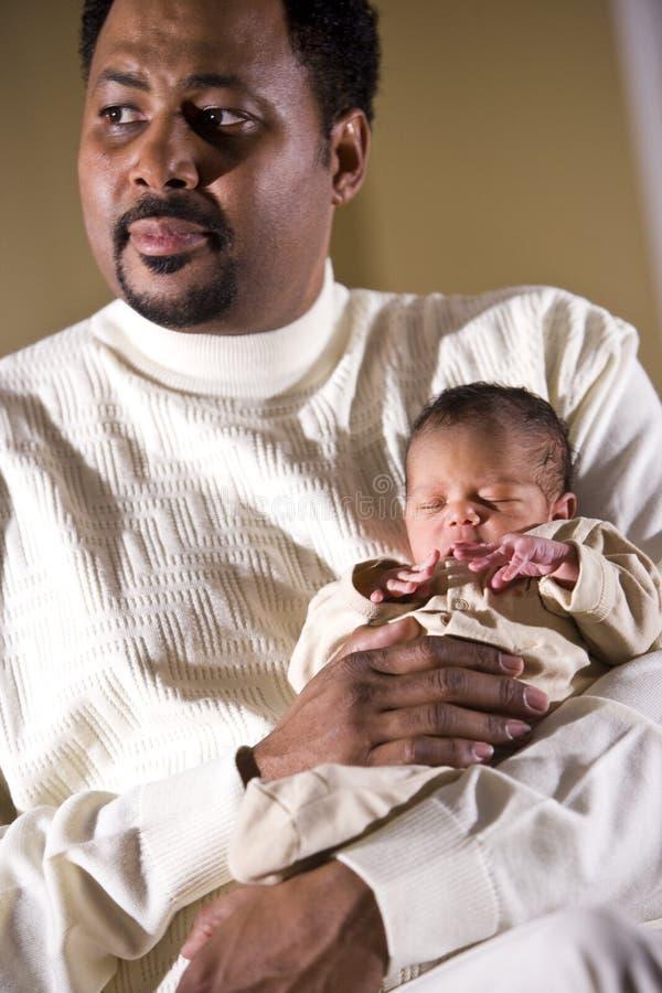 暂挂新出生微小的小父亲 库存照片