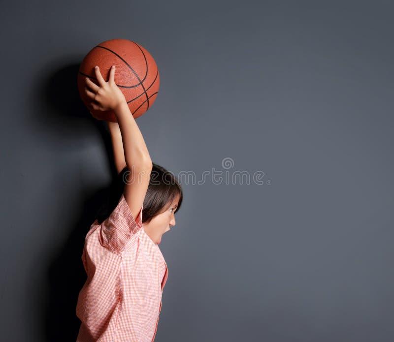 暂挂篮球的小男孩 免版税库存图片