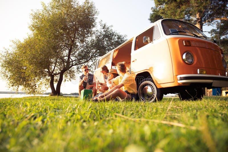 暑假、旅行、假期、旅行和人概念-获得微笑的年轻嬉皮的朋友在微型货车的乐趣 库存图片