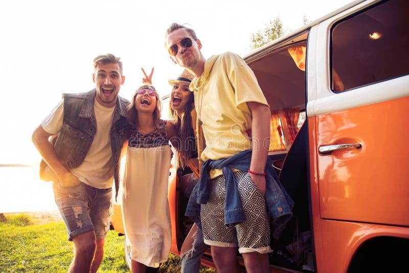 暑假、旅行、假期、旅行和人概念-获得微笑的年轻嬉皮的朋友在微型货车的乐趣 免版税库存照片
