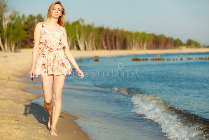 暑假。单独走在海滩的女孩。 免版税库存图片