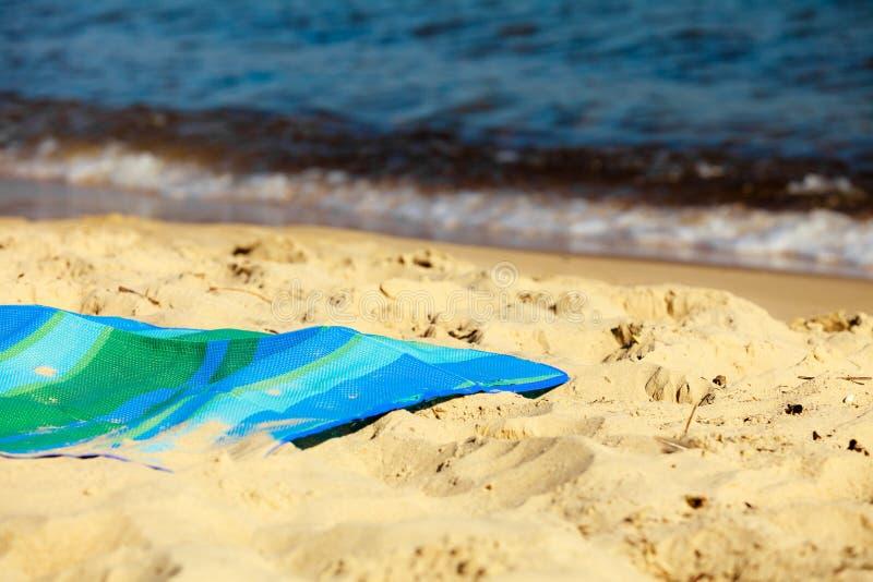 暑假。在海滩的空的蓝绿色席子 免版税图库摄影