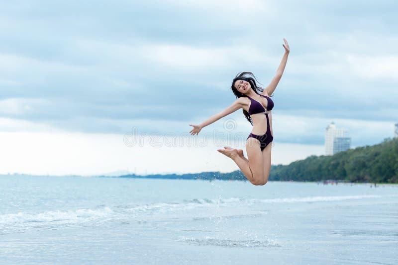 暑假假期概念 旅客在跳跃和享受放松的比基尼泳装的妇女生活方式 免版税库存图片