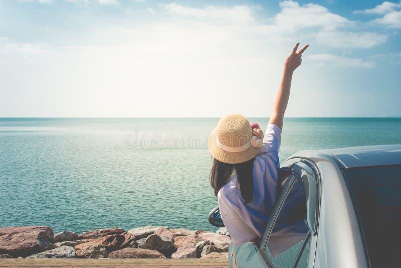 暑假和假日概念:在海的愉快的家用汽车旅行,画象妇女感觉幸福 库存图片