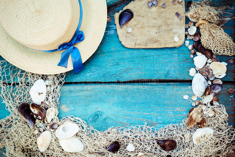 暑假放松与贝壳、捕鱼网、帽子、绳索、石头和被风化的木蓝色背景的背景题材与 库存图片