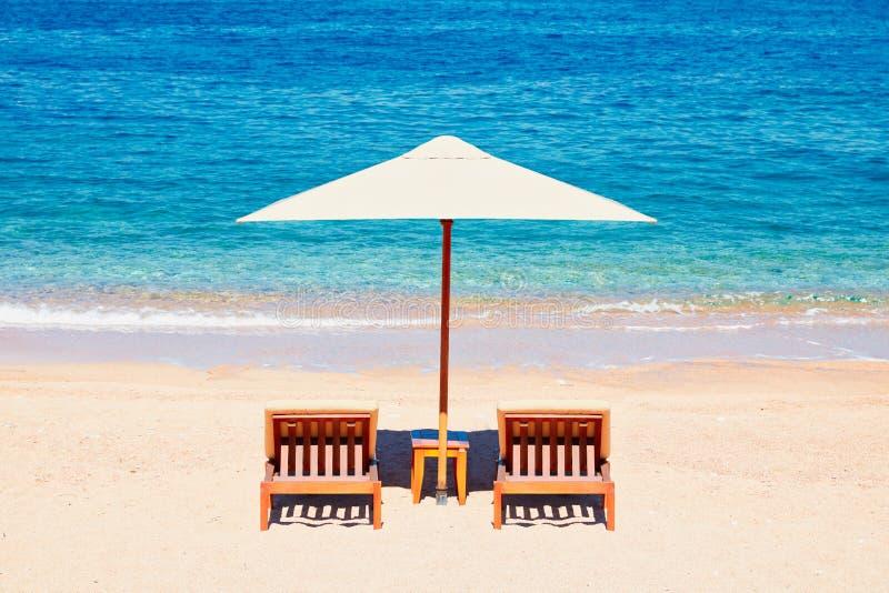 暑假背景墙纸:在帐篷下的两张海滩躺椅在海滩 免版税库存图片