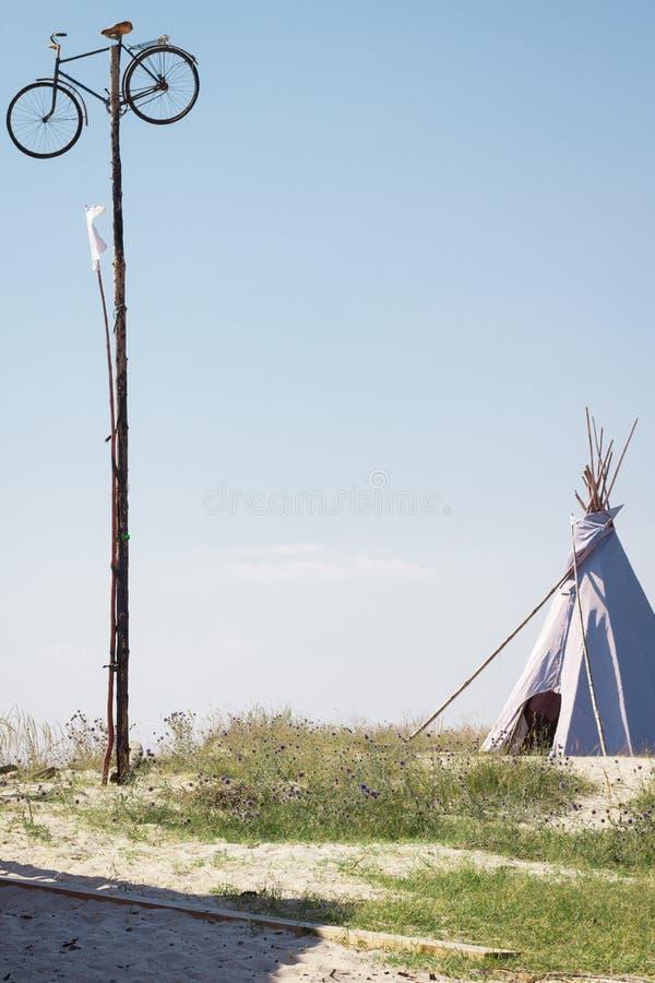 暑假野营的帐篷,印度圆锥形小屋小屋,在旗杆的自行车在干燥狂放的自然大草原干草原沙漠 免版税库存照片