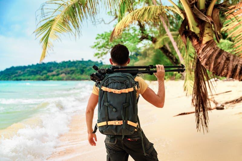 暑假,旅行和生活方式概念:有在手中拍在海滩的照相机的摄影师照片在背景自然 图库摄影