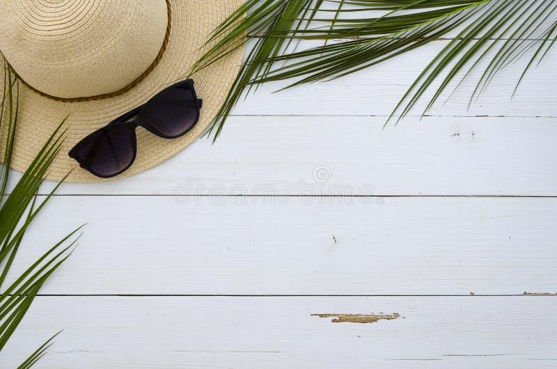 暑假,旅行,假日,海滩概念 太阳帽子、太阳镜和热带棕榈叶在白色木板 顶层 库存照片