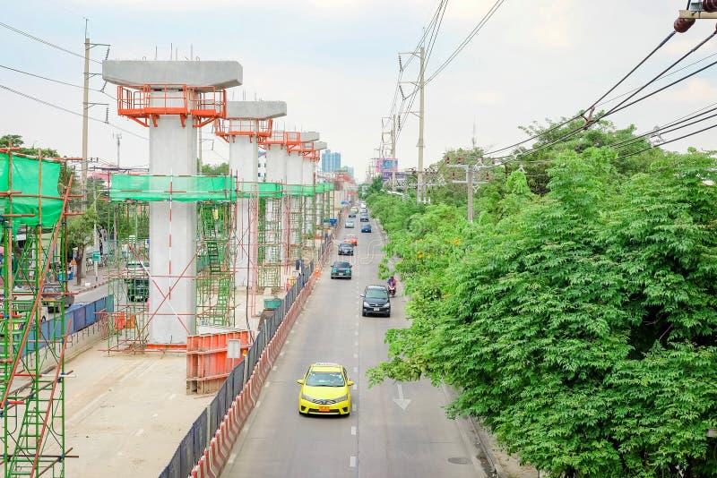 暖武里,泰国- 2019年6月08日:许多汽车、公共汽车和摩托车在Tiwanon路 建设中天空火车BTS 免版税图库摄影