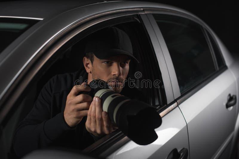 暗中侦察与从他的照相机的盖帽的男性无固定职业的摄影师 库存图片