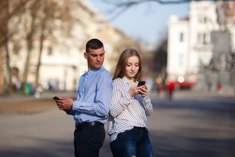 暗中侦察他的女朋友传讯的嫉妒的男朋友 免版税库存图片