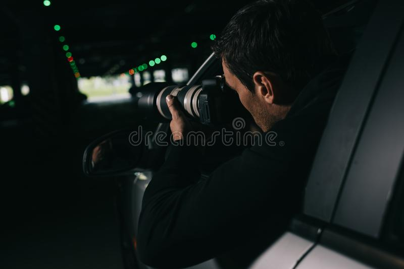 暗中侦察由与接物镜的照相机的男性无固定职业的摄影师背面图从他的 库存照片