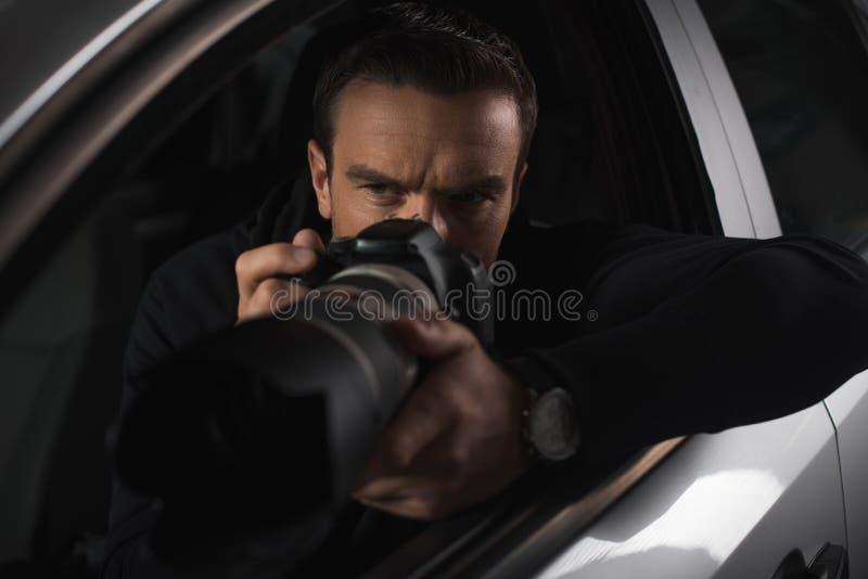 暗中侦察由与接物镜的照相机的被集中的无固定职业的摄影师从他的 免版税库存照片