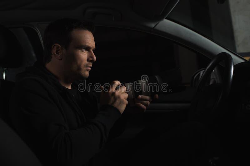 暗中侦察由与透镜的照相机的男性无固定职业的摄影师侧视图从他的 图库摄影