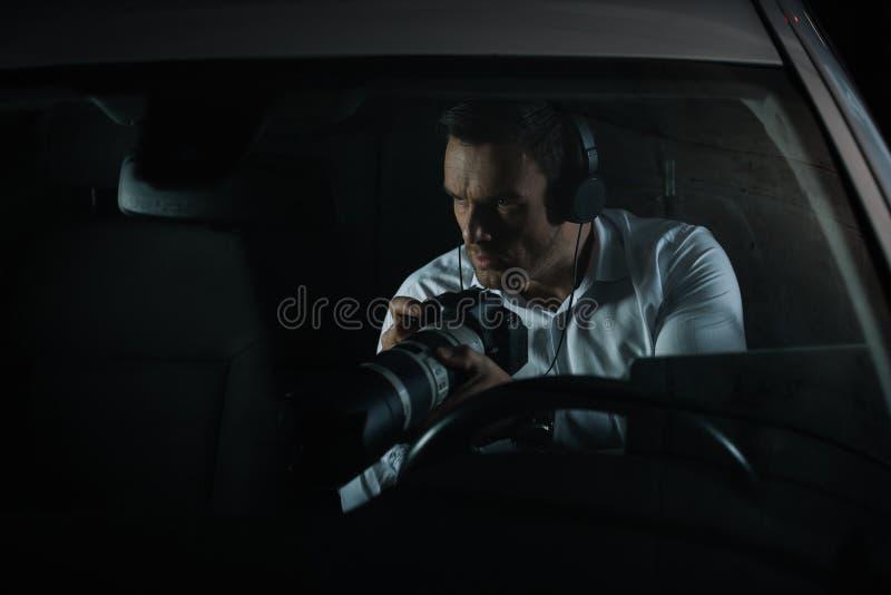 暗中侦察由与透镜的照相机的耳机的被集中的男性私家侦探 免版税库存图片
