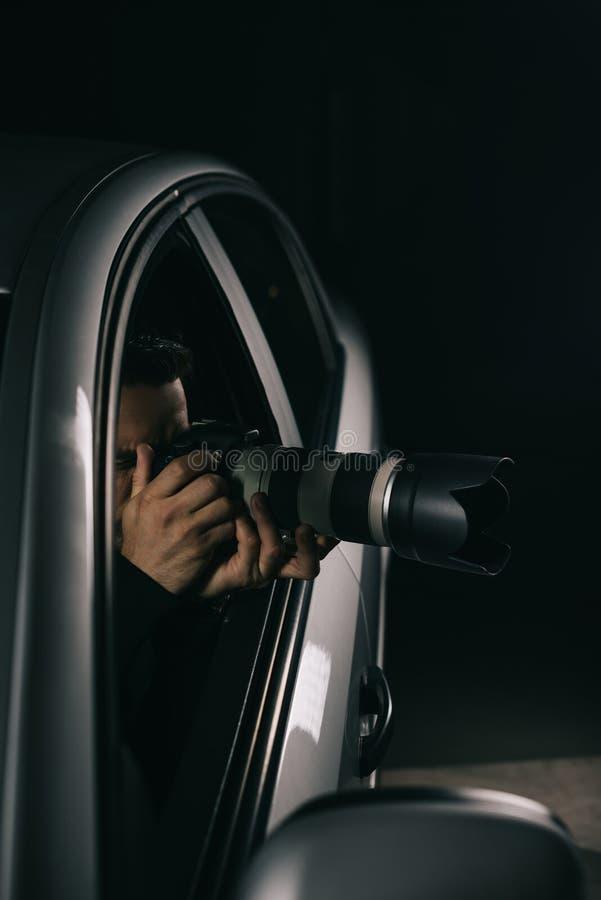 暗中侦察由与透镜的照相机的被集中的男性无固定职业的摄影师从他的 库存照片