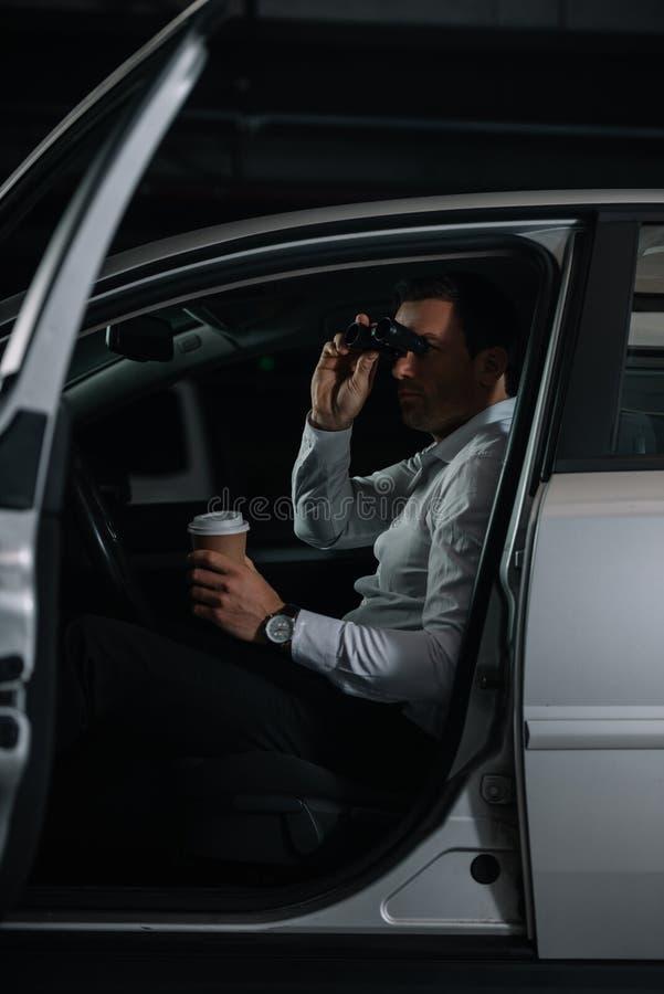 暗中侦察由双筒望远镜和饮用的咖啡的暗中进行的男性代理 免版税库存照片