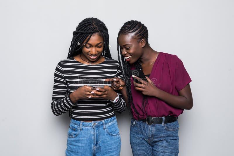 暗中侦察的两非洲年轻女人,当两个使用手机被隔绝在白色背景时 免版税图库摄影