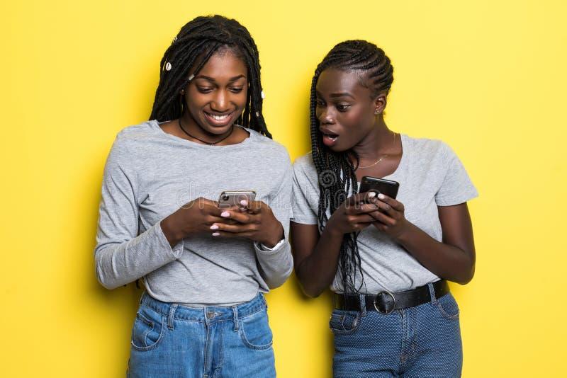 暗中侦察的两非洲年轻女人,当两个使用手机被隔绝在黄色背景时 免版税图库摄影
