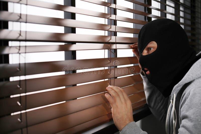 暗中侦察通过窗帘的被掩没的人 刑事罪 库存图片