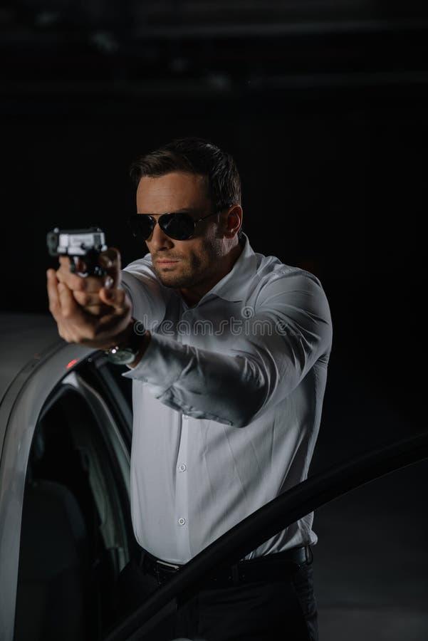 暗中进行的男性代理正面图在太阳镜瞄准的 免版税图库摄影