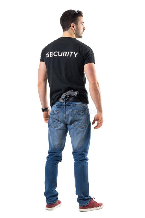 暗中进行的警察背面图有在他的附有的枪的后面传送带 图库摄影