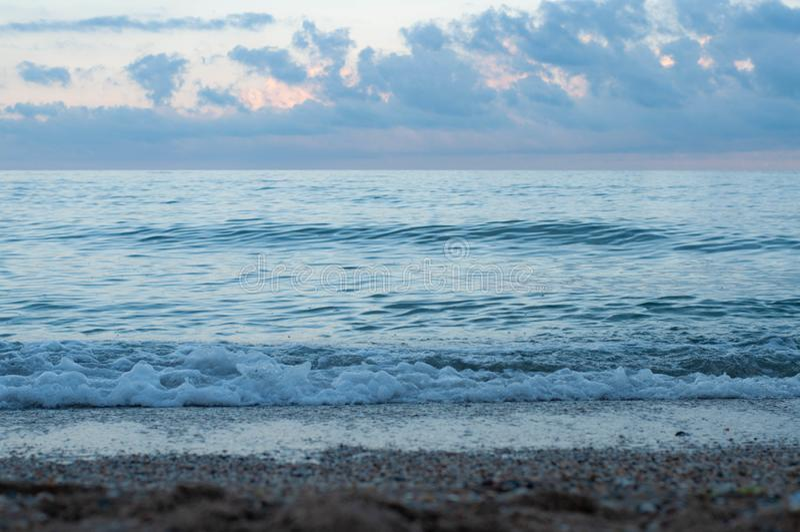 暗淡的海海浪在紫罗兰色蓝色晚上 免版税库存图片