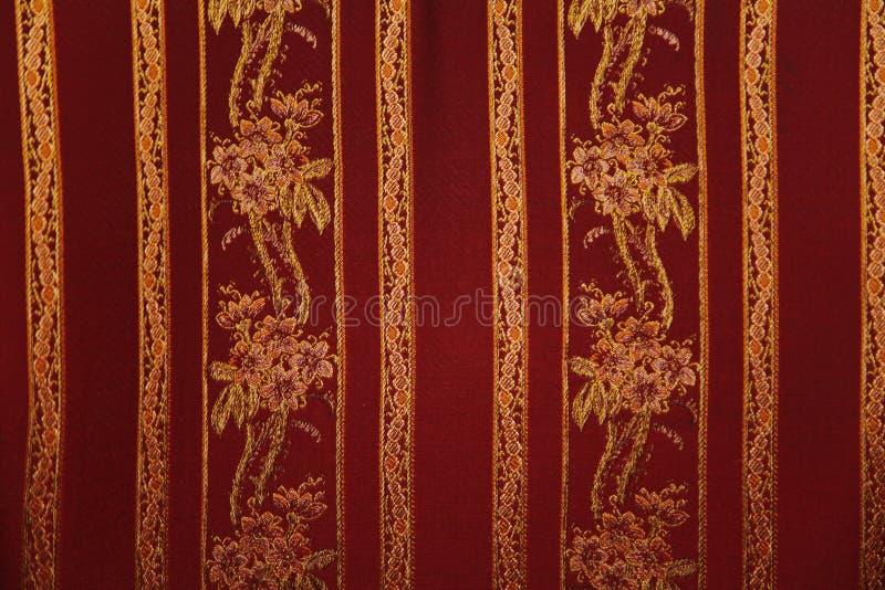 黑暗的丝织物纹理与一个过大的被绣的花卉样式的 库存图片