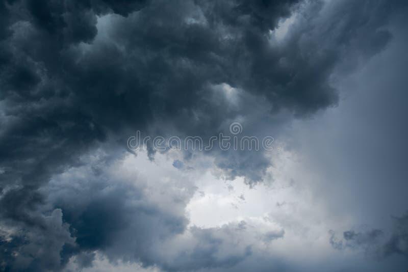 黑暗的云彩,阳光背景在雷暴前的通过非常黑暗的云彩背景,在旋风的白色孔dar 免版税库存照片