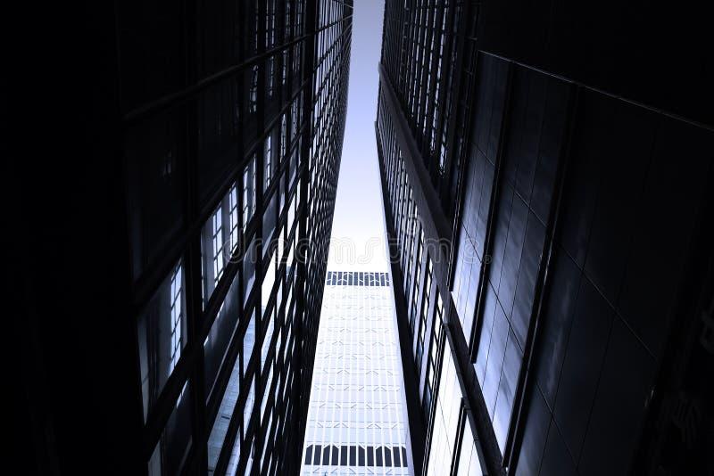黑暗的单调摩天大楼在有剧烈的光的香港市 库存图片