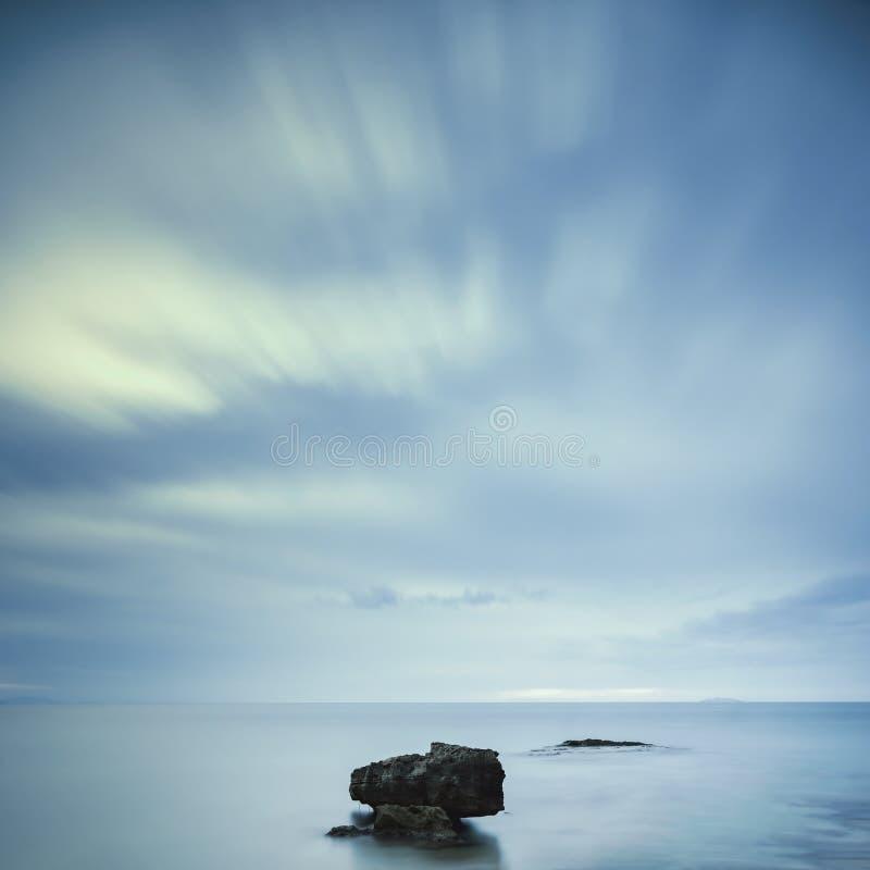 黑暗的岩石在蓝色海洋在恶劣天气的多云天空下 库存图片