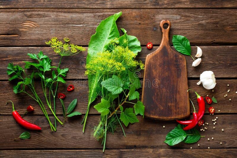 黑暗的木烹饪背景用各种各样的草本和香料,顶视图,土气 免版税库存图片