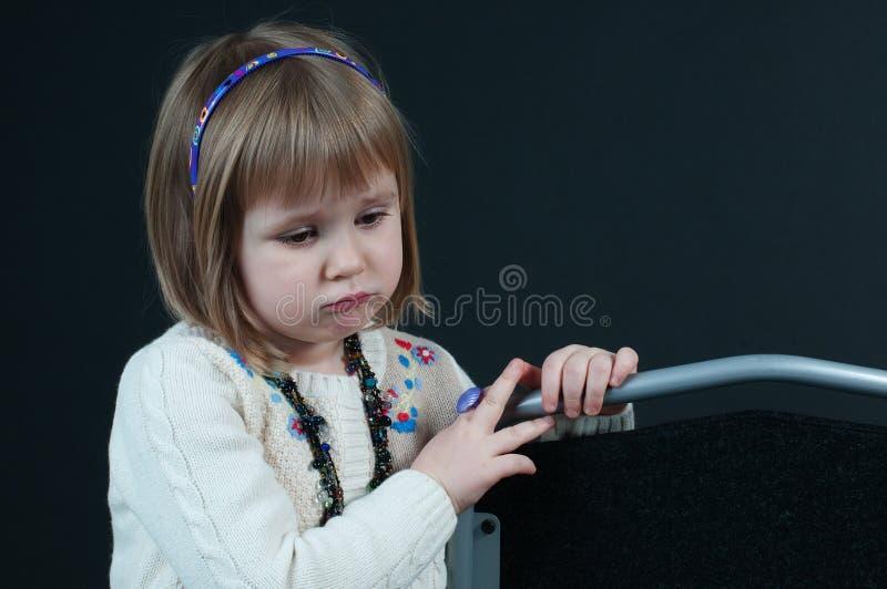黑暗的背景的不快乐的女孩 免版税库存图片