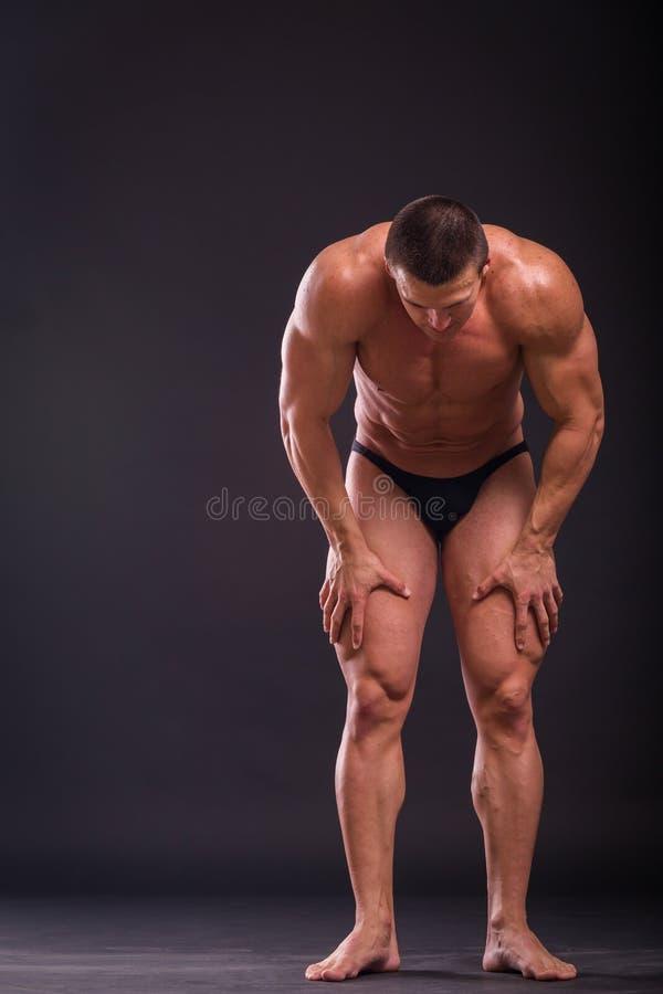 黑暗的背景的肌肉人 免版税图库摄影