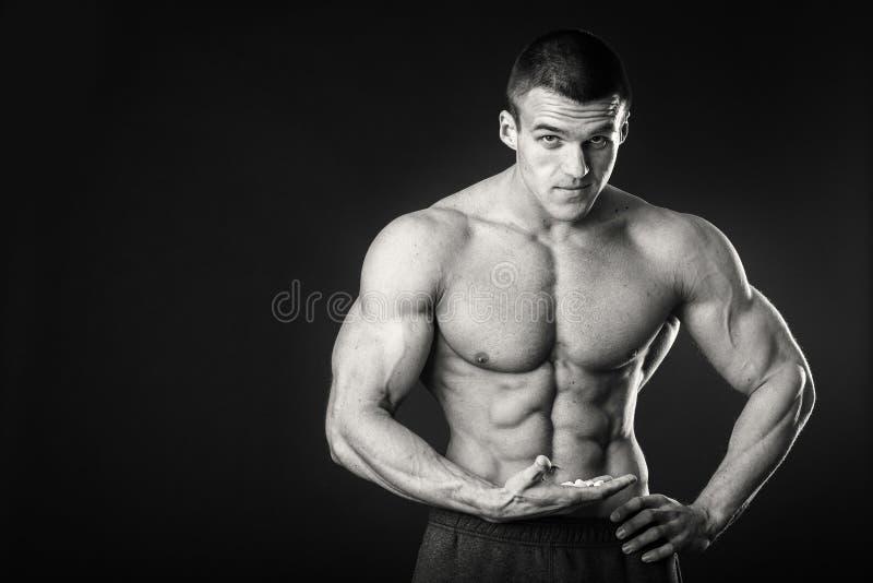 黑暗的背景的肌肉人 免版税库存图片