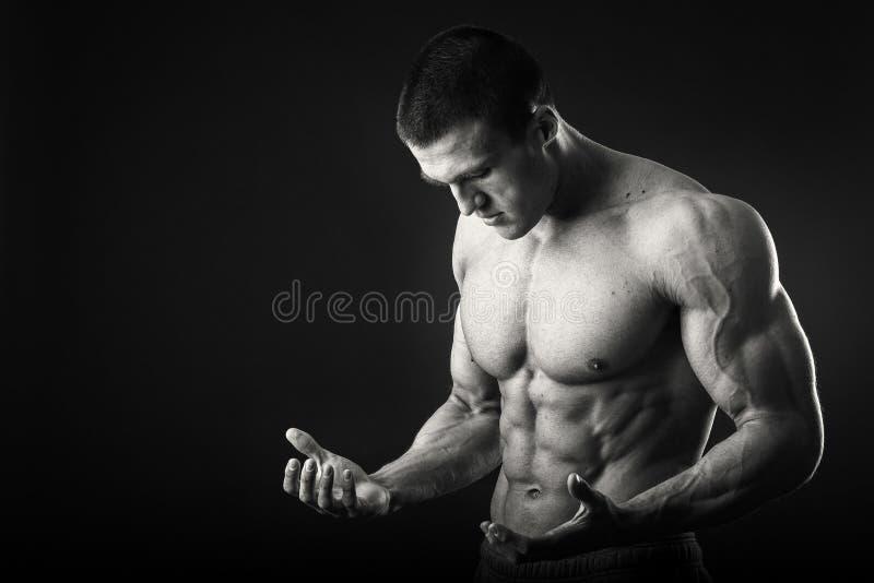 黑暗的背景的肌肉人 库存图片