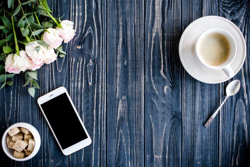 黑暗的被称呼的背景用咖啡、smartphote和玫瑰 库存照片
