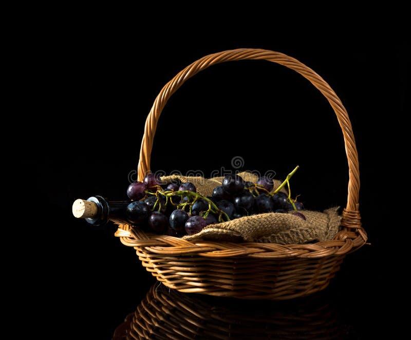 黑暗的酒杯和葡萄在篮子 库存照片