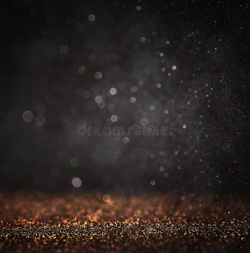 黑暗的闪烁葡萄酒点燃背景 轻的金子和黑色 defocused 库存照片