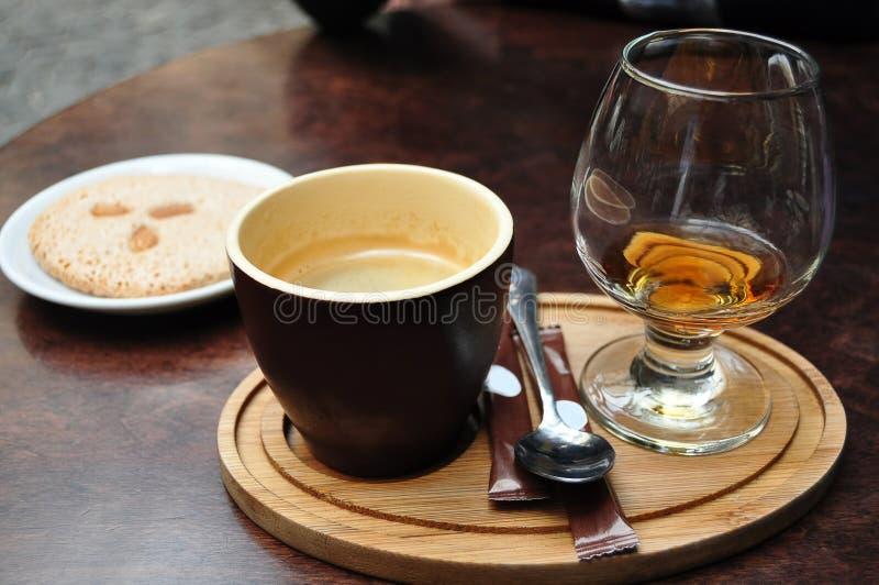 黑暗的陶瓷咖啡、杯科涅克白兰地和在一块白色板材的意大利杏仁cantuccini曲奇饼在咖啡馆的一张老木桌上 免版税库存照片