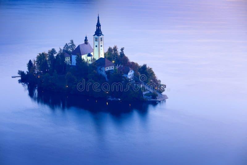 暮色平衡的光,流血,斯洛文尼亚 湖海岛、圣马丁天主教会和城堡与山脉,斯洛文尼亚, 免版税图库摄影