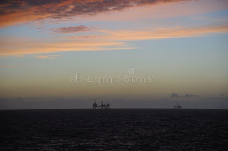 暮色红色天空和石油平台 免版税库存图片
