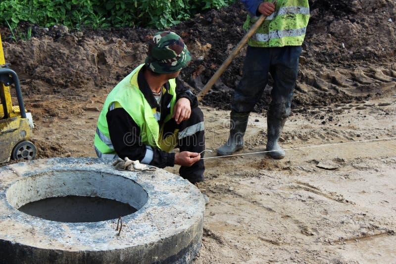 暴雨水决赛、开放舱口盖、沙子和石渣在高速公路的建筑时 工作者测量线与 免版税库存照片