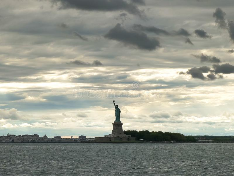暴风云和现出轮廓的自由女神像长远看法  库存图片