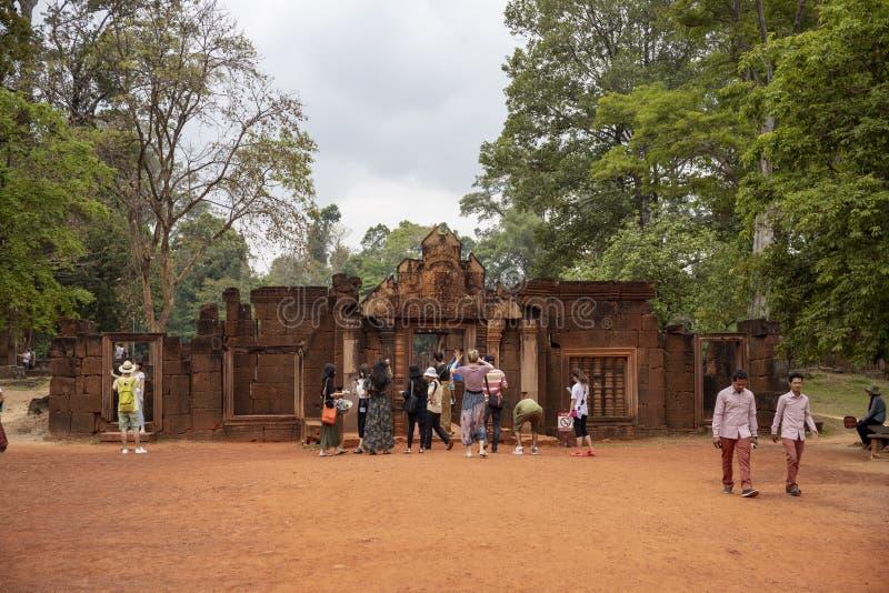 暹粒市,柬埔寨- 2018年3月29日:angkorian寺庙的女王宫游人 在寺庙入口的游览小组 免版税库存图片