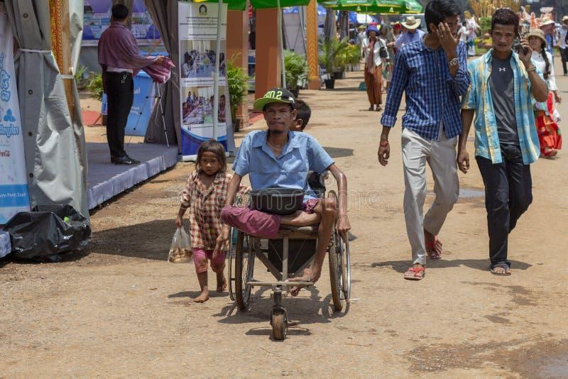 暹粒,柬埔寨, 2018年4月14日:可怜的孩子和残疾叫化子椅子的在公开市场街道上 库存照片