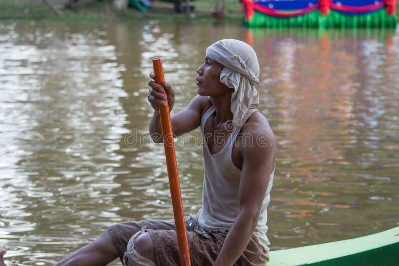 暹粒,柬埔寨- 2016年11月:小船竟赛者在实践期间的亚洲与桨在他的小船保持了平衡在东南亚 免版税库存图片